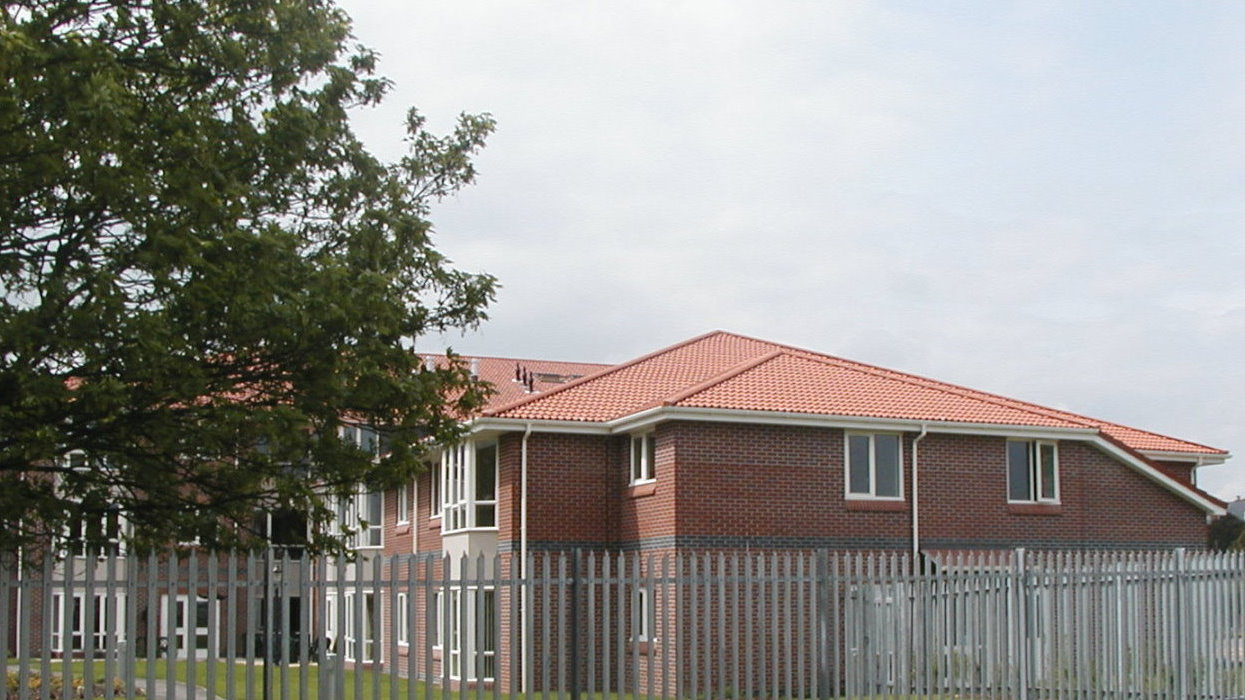 View of apartments with trees and a fence
