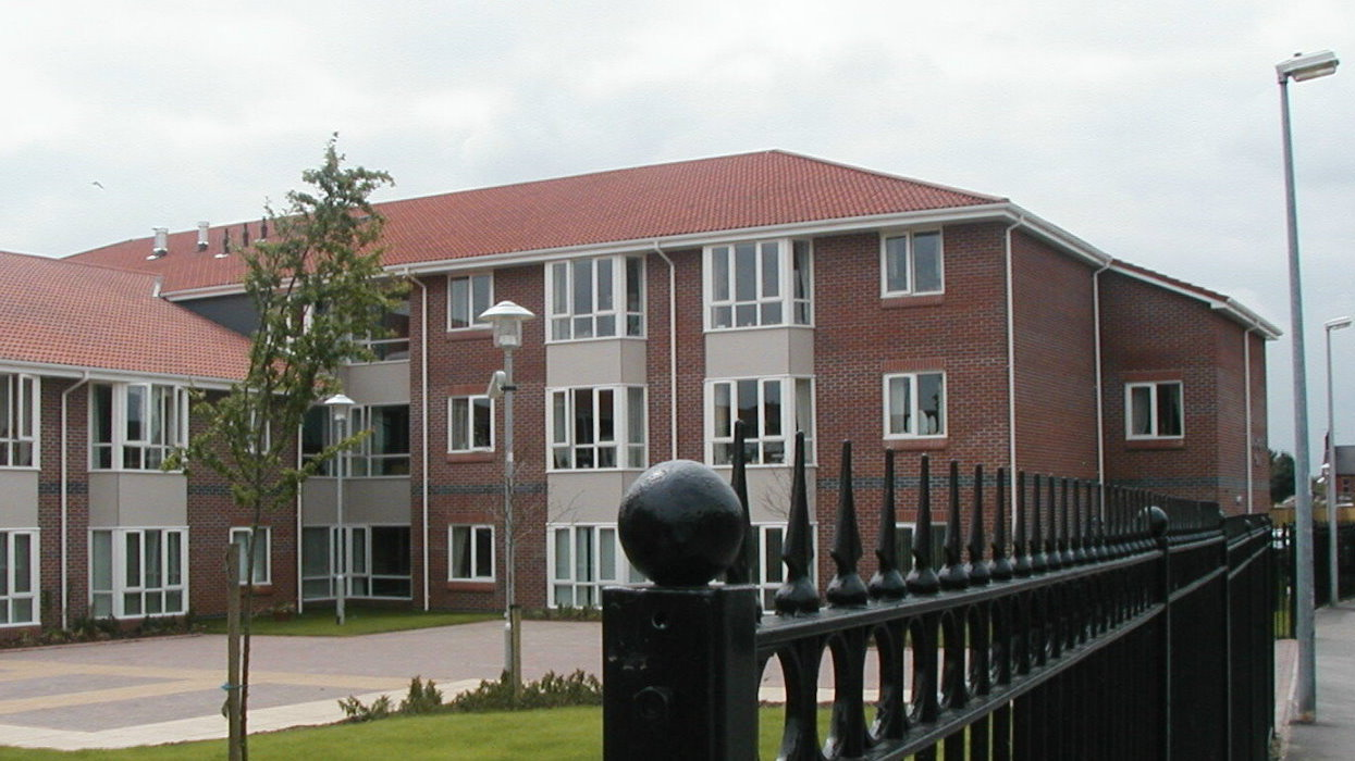view of apartments with trees and fence