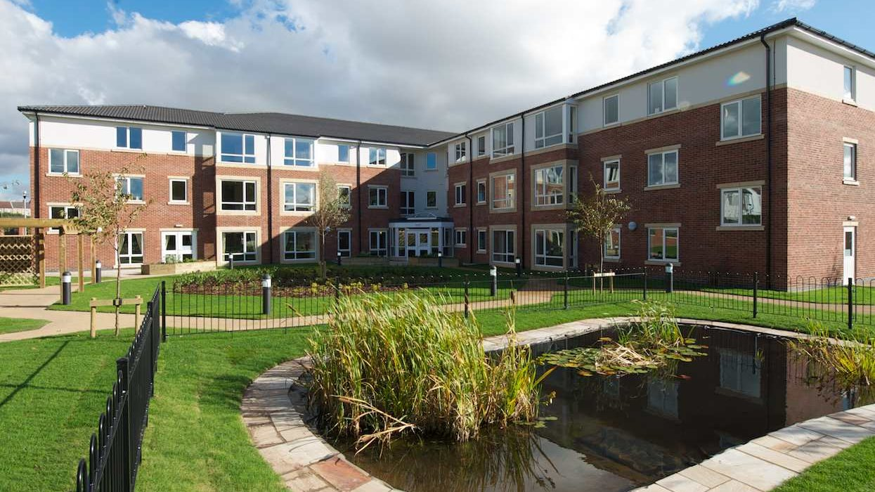 A view of flats with a pond in the forground