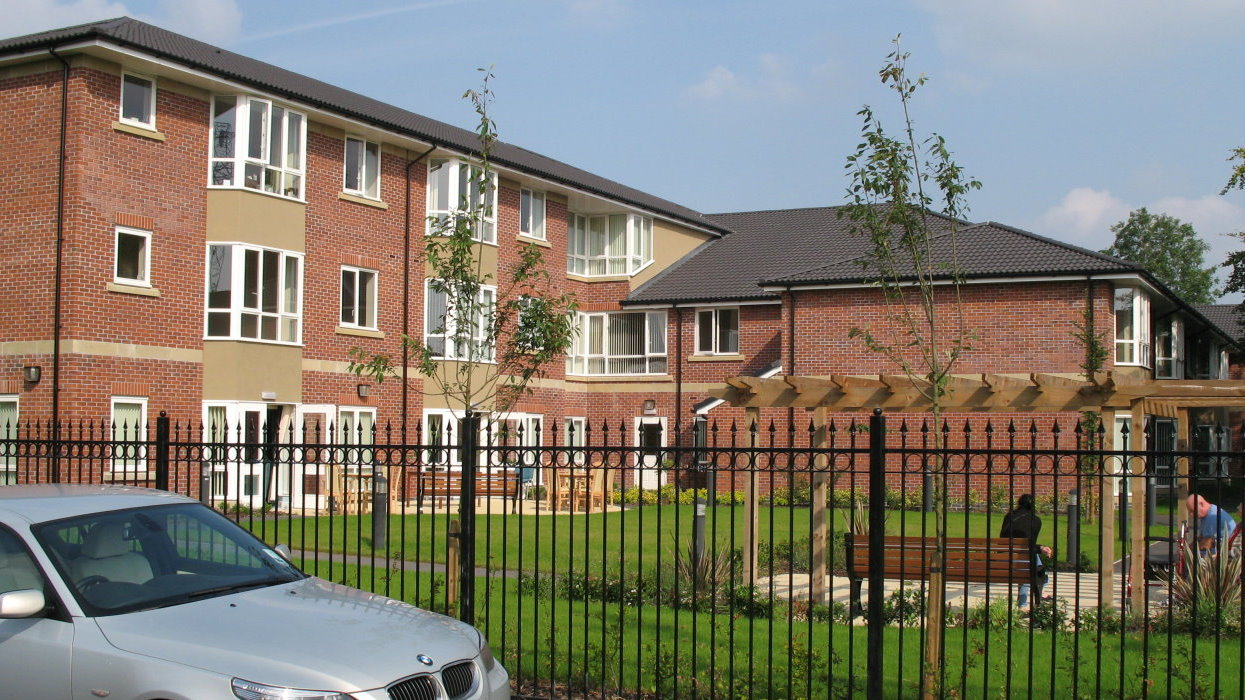 View from front with car, trees, fence and communal area