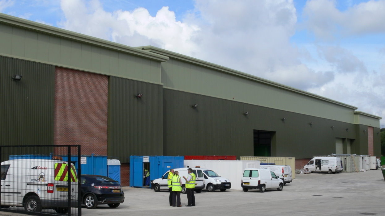 View of warehouse with cars and peole outside